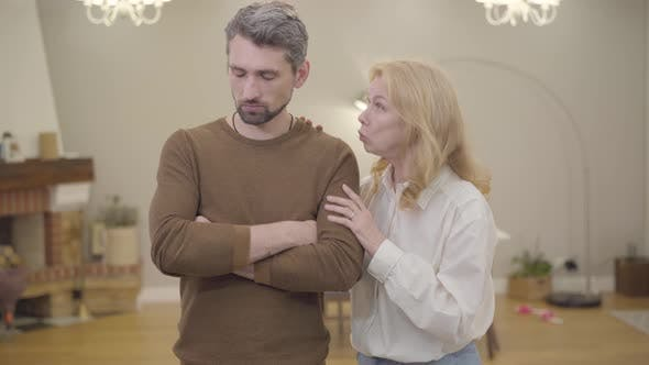 Thumbnail for Senior Blond Caucasian Woman Calming Down Bearded Man with Gray Hair at Home. Sad Adult Son Sharing