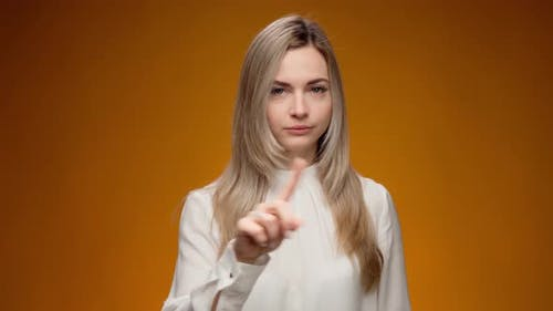Young Woman Wags a Finger Rejecting Something Against Yellow Background