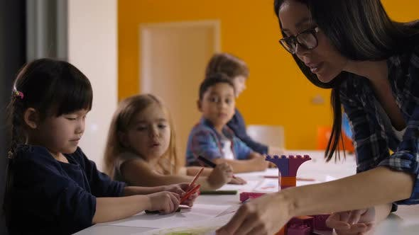 Kindergarten Teacher Helping Kids at Art Class