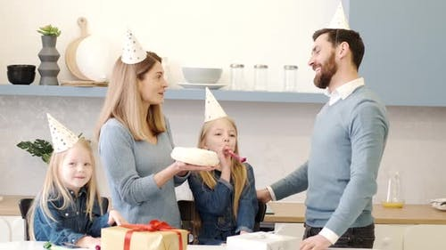 Family Congratulate Their Father with a Cake