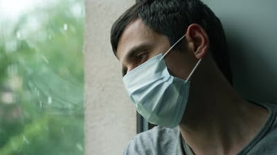 Sad Man in Mask Looks Outside the the Window