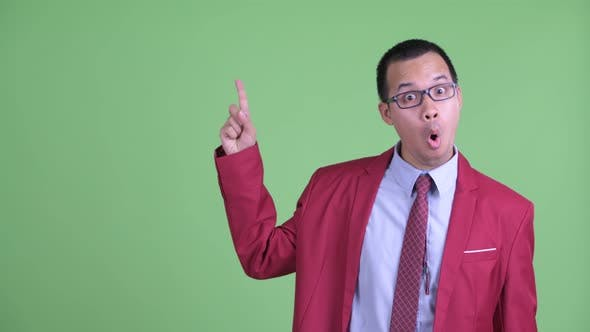 Thumbnail for Happy Asian Businessman with Eyeglasses Pointing Up and Looking Surprised