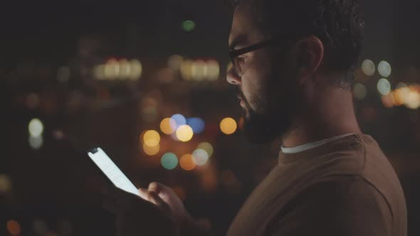 Businessman Messaging on Smartphone in Dark Office