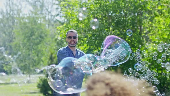 Thumbnail for Joyous Man Blowing Large and Small Bubbles for Kids