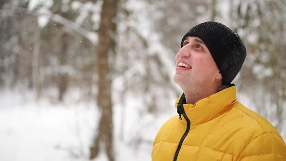 Thumbnail for A Man in a Yellow Jacket Looks at the Snow in the Winter in the Woods and Smiles in Slow Motion