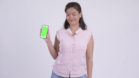 Thumbnail for Young Happy Asian Businesswoman Showing Phone and Giving Thumbs Up