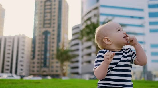Thumbnail for Baby Boy Infant Laughing in the Summer Sitting on the Grass on the Background Buildings