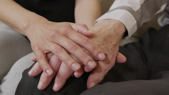 Thumbnail for A Young Womans Hands Comforting a Old Man Hands. Closeup.