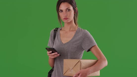Thumbnail for Woman checks shipping service app on phone while holding package on greenscreen