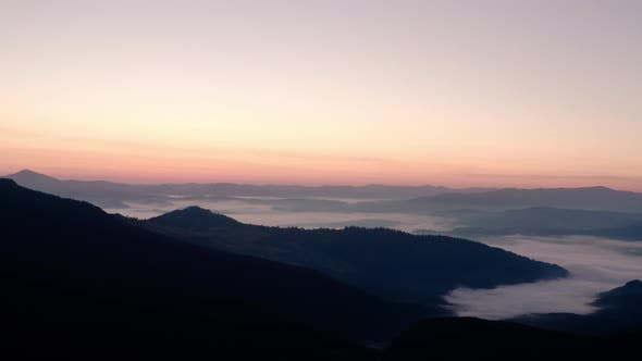 Aerial Drone Still View. Sunrise or Sunset in the Mountains, Flying Over the Trees in the Sun