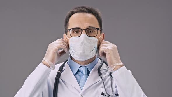 Thumbnail for Handsome Lab Technician in Medical Uniform Takes Off Protective Mask and Smiles