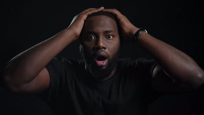 Stressed Afro Guy Posing on Black Background
