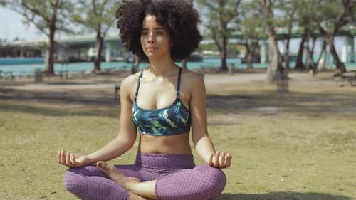 Content Woman Meditating in Sunlight in Park