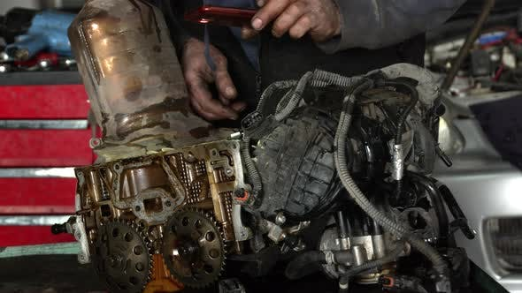 Workshop Master Checks Cylinder Head Of A Dismantled Vehicle Engine Through His Eyes