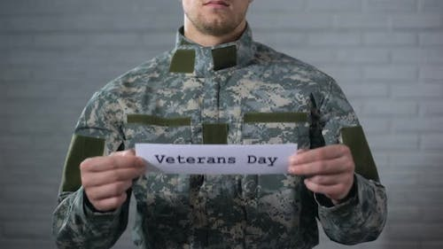 Veterans Day Word Written on Sign in Male Soldier Hands, Gratitude and Respect