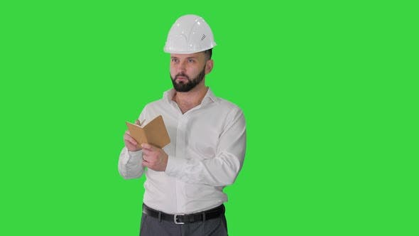 Confident Mature Man in Formalwear and Hardhat Writing Down Notes on a Green Screen Chroma Key