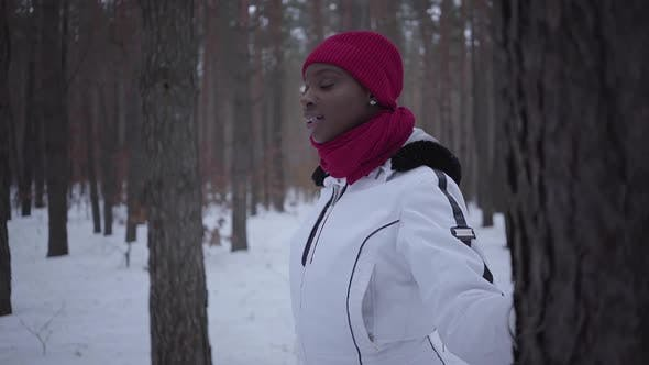 Cover Image for African American Girl Dressed Warm Wearing a Red Hat, Scarf and White Jacket Standing in Winter
