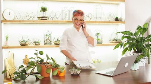 Female Florist Talk on Mobile Phone While Working