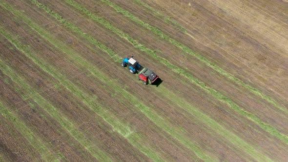 Thumbnail for Traktor mit Rundballenpresse entlädt einen frischen Weizenballen