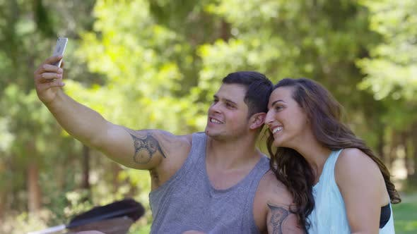 Thumbnail for Couple outdoors taking cell phone selfies