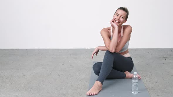 Beautiful Woman Resting on Exercise Mat