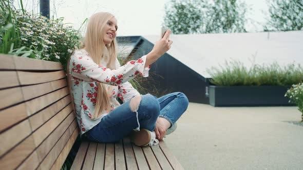 Thumbnail for Frau macht Video anruf auf grünem Dach.