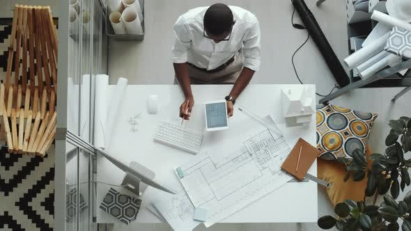 Top Down of Afro-American Architect Drawing Floor Plan and Using Tablet