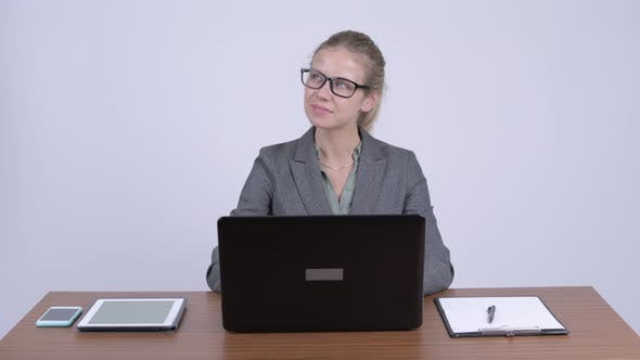 Thumbnail for Young Happy Blonde Businesswoman Thinking While Using Laptop at Work