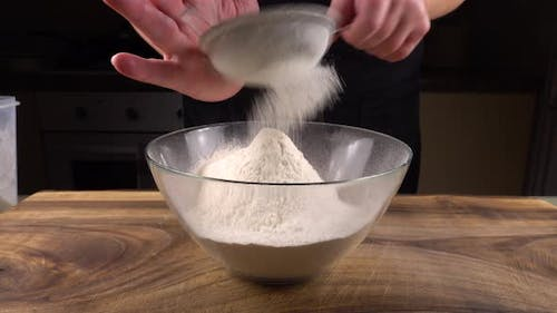 Sifting flour through a sieve into a glass bowl in the kitchen
