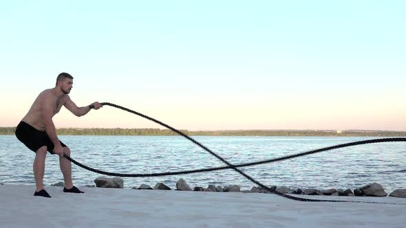 Thumbnail for Sportsman Conducts Training with the Ropes on the Sandy Shore. Slow Motion