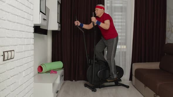 Senior Man in Sportswear Using Orbitrek in Living Room Doing Sport Training Cardio Exercises at Home