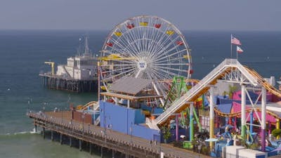 Aerial of Ferris wheel and amusement park rides at Pacific Park