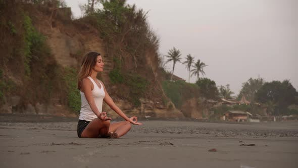 Thumbnail for Young Woman Meditating in Lotus Pose on Ocean Shore