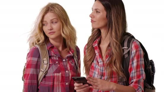 Thumbnail for Portrait of 2 female hikers using phone to navigate location on white copy space
