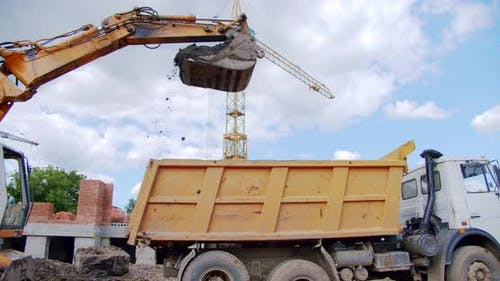 Excavator Loads Sand Into a Truck Body at a Construction Site, Industry