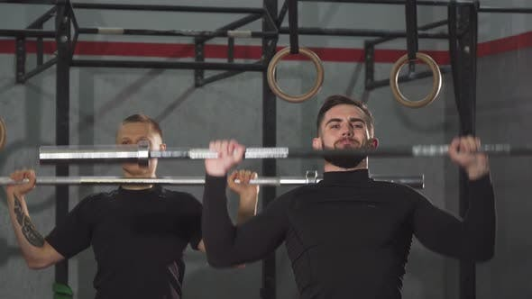Thumbnail for Male Crossfit Athletes Warming Up at the Gym Lifting Barbells