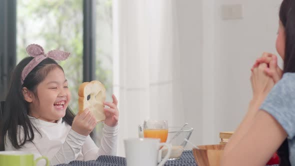 Asian daughter pick and play bread laughing smile with parents while eating corn flakes.