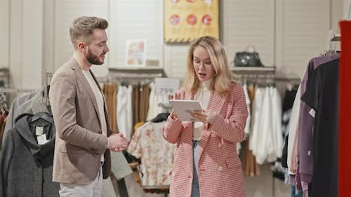 Man Shopping For Clothes With Female Stylist