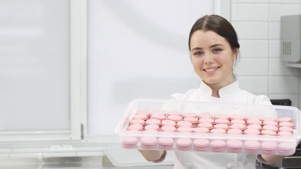 Thumbnail for Professional Confectioner Smiling Holding Out Tray Full of Macaroons To the Camera