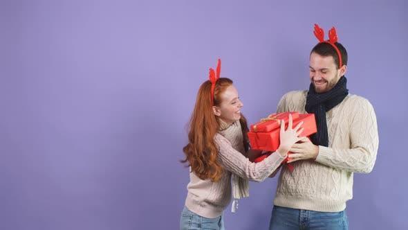 Fröhliches junges Paar, das Spaß mit Weihnachtsgeschenken im Studio auf lila Hintergrund hat.