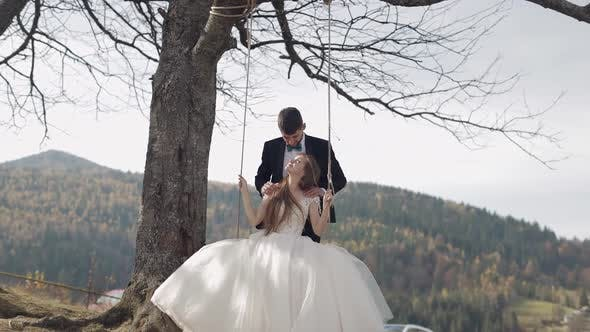 Cover Image for Newlyweds. Caucasian Groom with Bride Ride a Rope Swing on a Mountain Slope