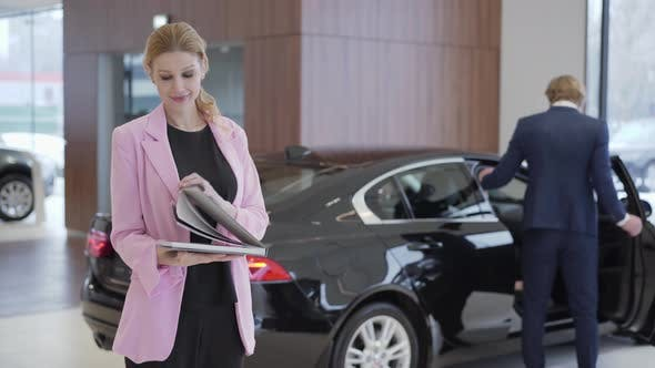 Cover Image for Portrait of Pleasant Cute Girl in Pink Jacket with a Big Book About Cars in Front of Couple Choosing