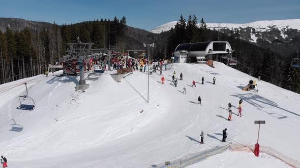 Thumbnail for Aerial View Crowd of Skiers Skiing on Peak Ski Slope Near Ski Lifts. Ski Resort