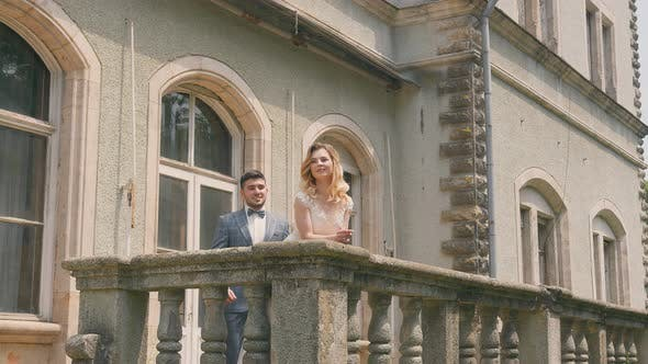 The Groom Approaches the Bride Standing By the Stone Balcony and Hugs Her From Behind. Happy
