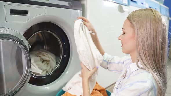 Women s Hands Load Laundry Clothes Into the Washing Machine in the Public Selfservice Laundry