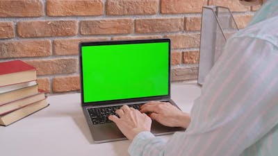 Unrecognizable Woman Typing on Laptop with Green Screen