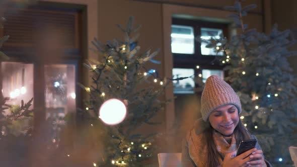 Thumbnail for Woman Sits in an Outdoor Cafe Terrace in Winter and Chatting in Social Networks, Using Her