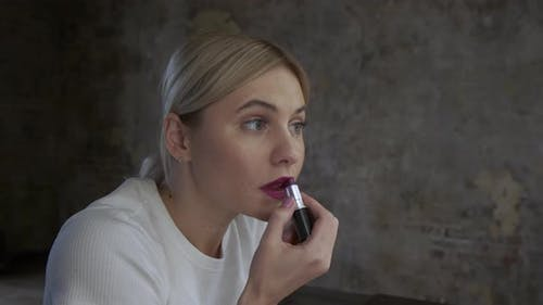Woman Paints Her Lips With Lipstick On A Black Background, blonde young woman