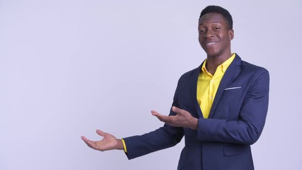 Young Happy African Businessman Showing Something