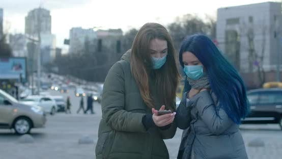 Cover Image for Young Women in Protective Masks Using Smartphone. Brunette Girl Moving Aside As Her Friend Coughing
